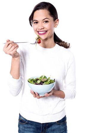 ensalada verde: La mujer joven sana que come la ensalada verde sobre blanco