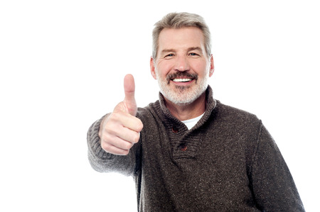 Bearded senior man showing thumbs up sign