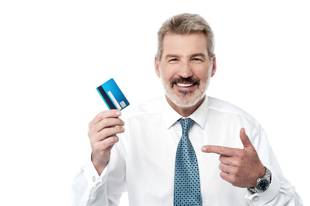 debit card: Senior man showing and pointing debit card
