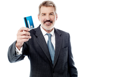displaying: Smiling male executive displaying credit card over white