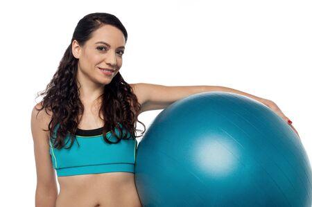 swiss ball: Pretty woman holding swiss ball on her hip Stock Photo