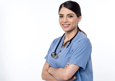 Médico mujer sonriente posando con los brazos cruzados Foto de archivo