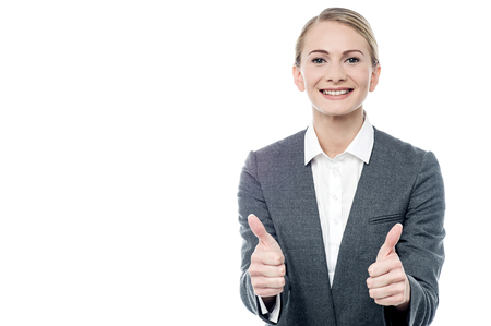 posing  agree: Young businesswoman gesturing success to her colleagues