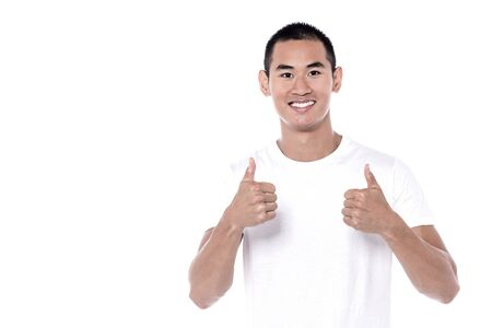 posing  agree: Young man showing double thumbs up signature