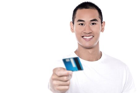 debit card: Young man displaying his debit card to camera