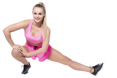 sports wear: Young lady stretching her legs in sports wear