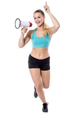 ropa deportiva: Young woman in sportswear holding megaphone Foto de archivo