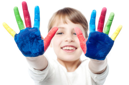kids painted hands: Smiling girl showing colorful palms
