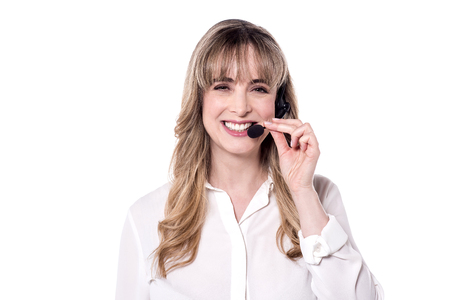 head support: Customer support executive adjusting her head phone. Stock Photo