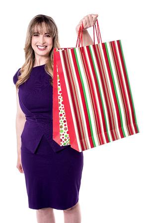 party wear: Pretty woman in party wear showing shopping bag