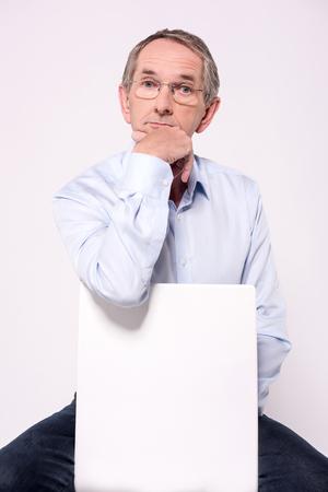 ad: Pensive senior man sitting behind ad board
