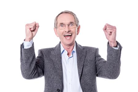hombre mayor alegre apretando los puños en la alegría. Foto de archivo