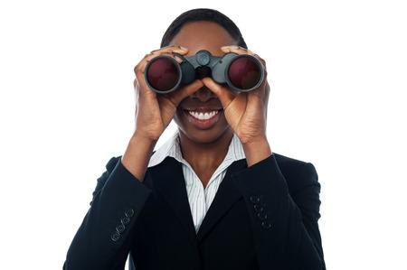 looking through an object: Smiling business woman using binocular