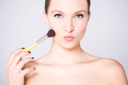 bare shoulders: Bare shoulders attractive lady  applying blusher