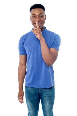 shush: Young guy showing be silent gesture.