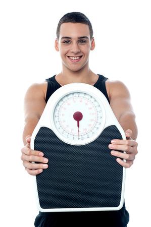 weigh machine: Macho guy showing weight machine