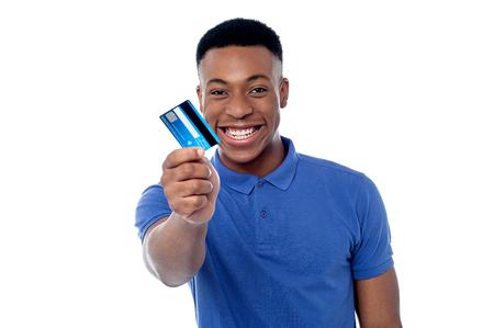 Glimlachende jonge jongen die creditcard toont