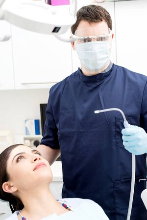 Male orthodontist attending patient