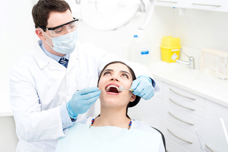 Male doctor examining decayed tooth of patient Stock Photo