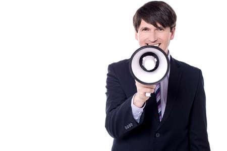 businessman using a megaphone: Businessman using megaphone to make an announcement