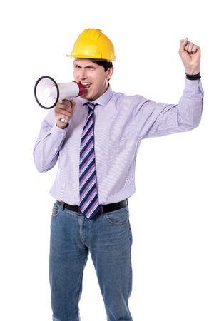 making an announcement: Construction worker making announcement with megaphone. Stock Photo