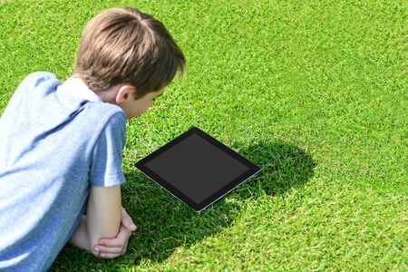 Cute boy lying on grass in park and using tablet pc photo