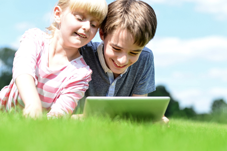 Brother and sister using tablet PC on the grass in summer park. photo