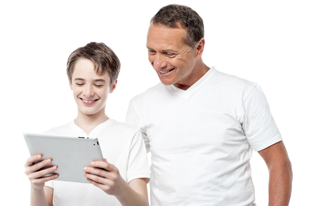 Dad and son using a tablet pc over white background. photo