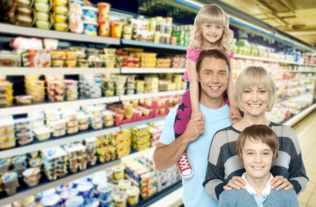 Image of young family grocery shopping in supermarket photo