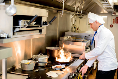 non uniform: Chef frying a dish in hotel kitchen