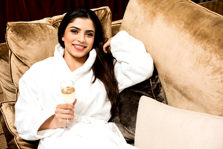 bath gown: Young relaxed lady luxurious couch with wine glass