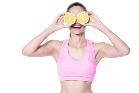 underarms: Young woman is holding slices of oranges to her eyes Stock Photo