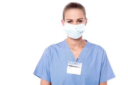 surgical mask: Beautiful face of a woman doctor wearing surgical mask.