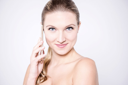 bare shoulders: Beautiful woman talking over her phone with bare shoulders Stock Photo