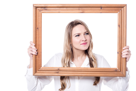 old frame: Confused young woman looking sideways holding an old frame