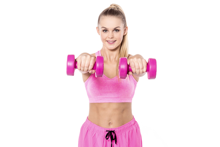 free weights: Pretty happy young woman exercising with free weights. Stock Photo