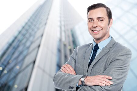 Handsome elegant businessman in front of office building photo