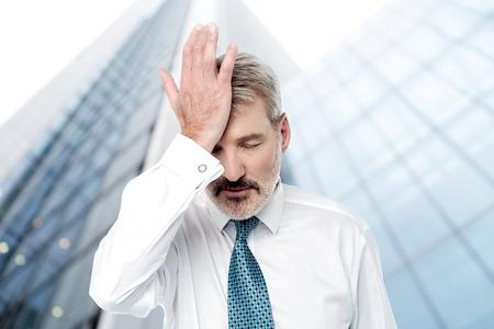 hand on forehead: Senior corporate executive keeping hand on forehead Stock Photo