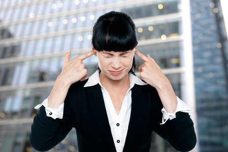 irritated: Irritated businesswoman closing her ears with fingers Stock Photo