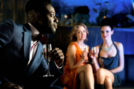 Young girls staring at attractive young male in night club photo