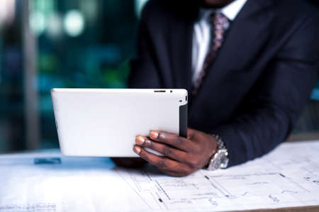 Cropped image of businessman working on tablet PC photo