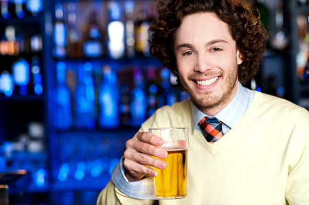 Happy young man at bar holding glass of beer photo