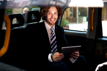 Handsome young businessman inside taxi with touch pad photo