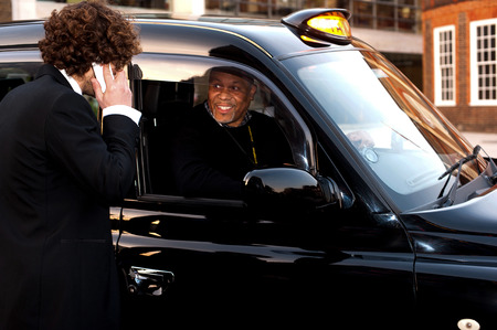Young businessman talking to african taxi cab driver photo