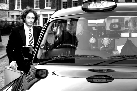Smart young businessman talking to taxi cab driver photo
