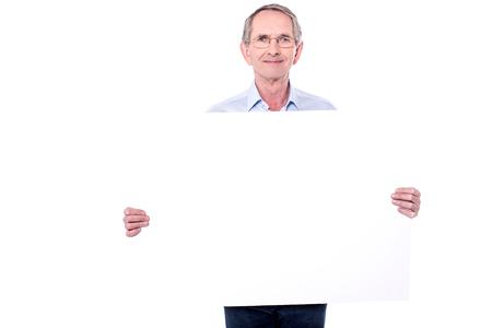 Matured man standing behind blank placard.