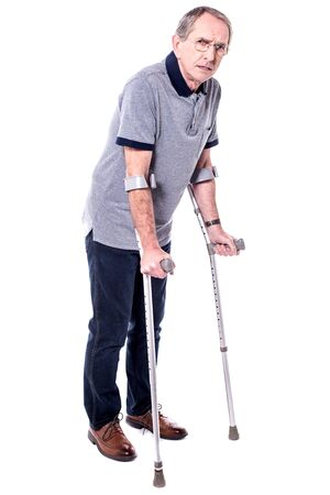 Full length image of mature man with crutches.