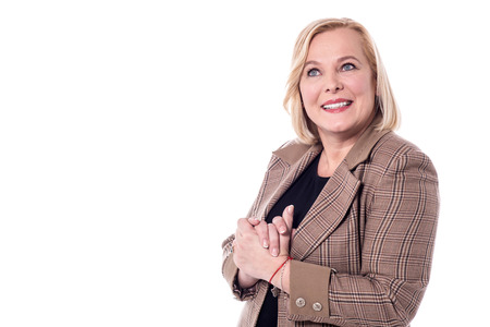clasped hands: Confident woman looking at camera with clasped hands.