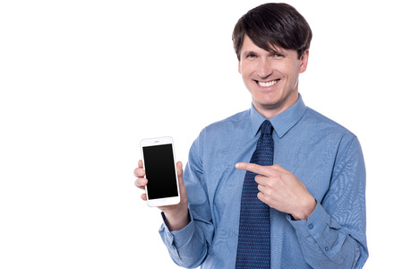 Smiling corporate man holding smart phone and pointing finger to it. Stock Photo