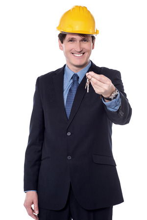 Smiling real estate agent showing keys to camera.